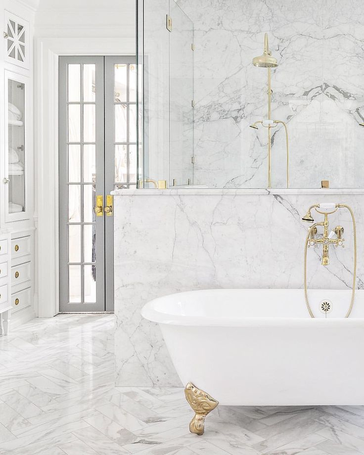Marble Bathroom With White And Brass Claw-foot Tub