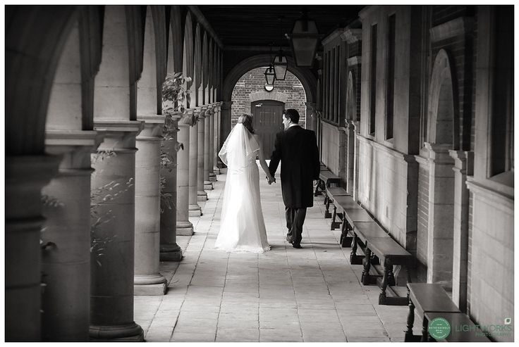 Bride and groom walking in the cloisters at Sidney Sussex College Cambridge