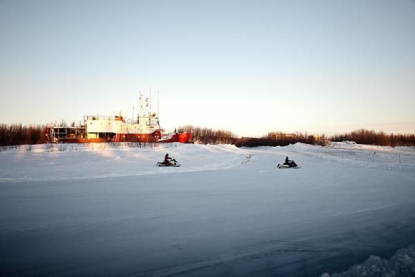 Snowmobilers riding on the Mackenzie River past the GSI Mariner