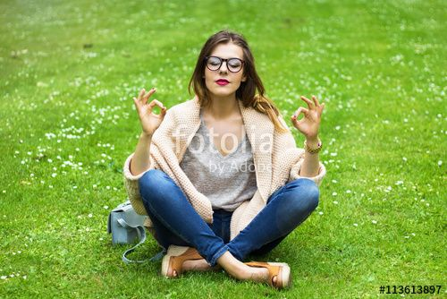 Young peaceful girl meditates in the park
