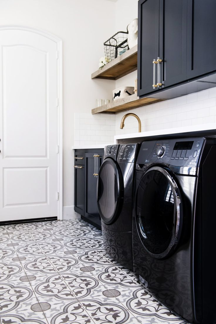 Dark cabinetry paired with black washer and dryers in this playful yet chic laundry  room Savvy
