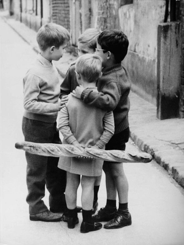 Meeting around a baguette - France, 1950 | My baguette always seemed to be missing a piece.. Very strange.