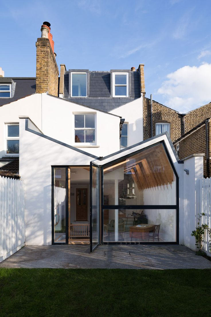 "London house extension with a ""butterfly"" roof and exposed wooden rafters"