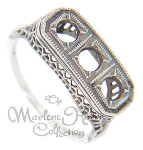Filigree designs decorate this 14K white gold antique style engagement ring mounting. The ring measures 8mm in width and can hold a total of three round stones 3.75mm in diameter. Made from the original master mold, the mounting can be ordered in 14K or 18K white and yellow gold as well as platinum. Actual prices depend on the current market value of the precious metal used.