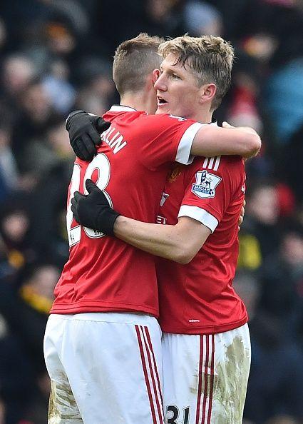Manchester United's German midfielder Bastian Schweinsteiger embraces Manchester United's French midfielder Morgan Schneiderlin after the English...