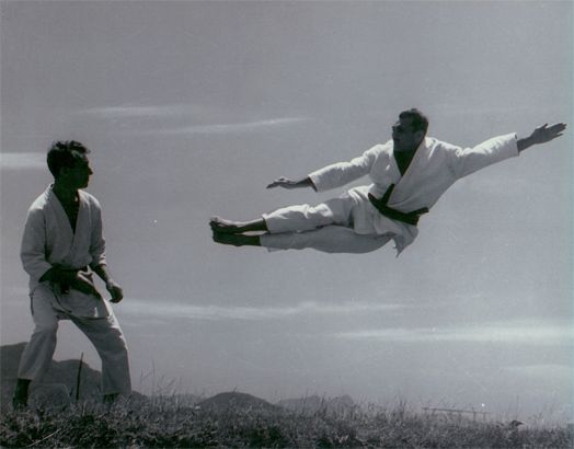 Helio Gracie practicing his double flying kick on Carlos Gracie
