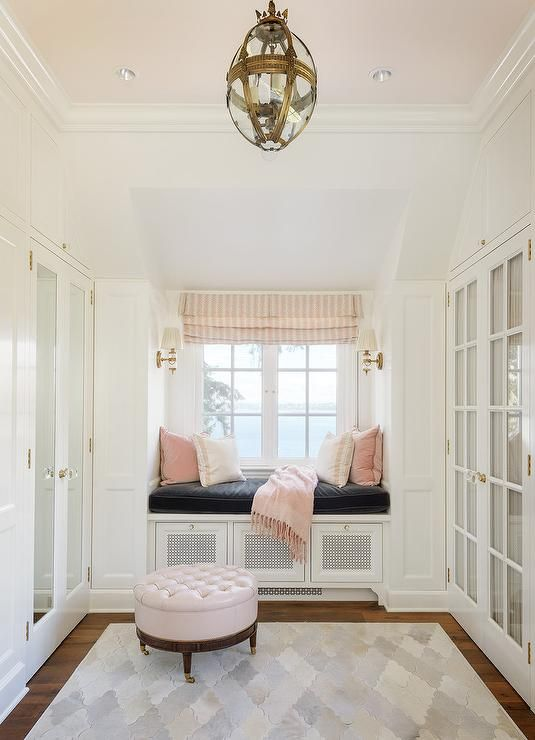 White and Pink Closet with Pink Ceiling - Transitional - Closet-White and pink walk in closet features a pink painted cieling accented with a glass and brass pendant light illuminating a round pink leather tufted storage ottoman on caster legs placed atop a hide quatrefoil rug facing mirrored wardrobe cabinet doors, Chic closet boasts a built-in window seat lined with a black velvet cushion and blush pink velvet pillows placed under windows dressed in pink...