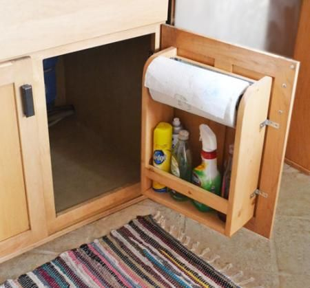Kitchen cabinet door organizer for cleaning supplies and paper towels.