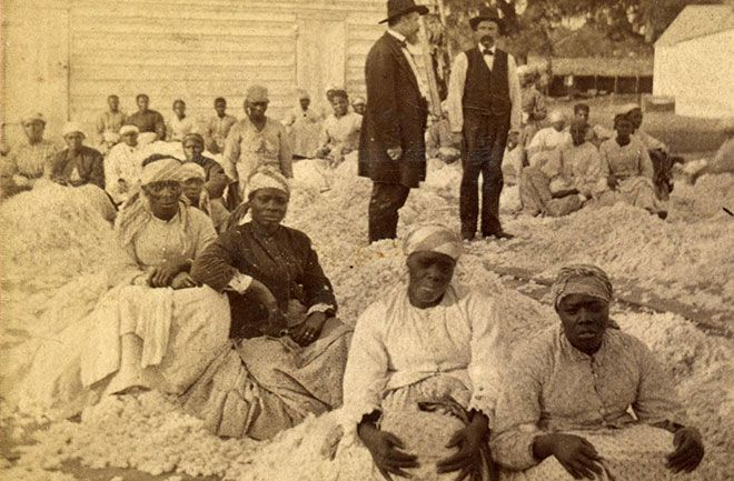Rare Photos Show Civil War Life : Discovery News.  A group of African American women sitting on piles of cotton with two white male overseers