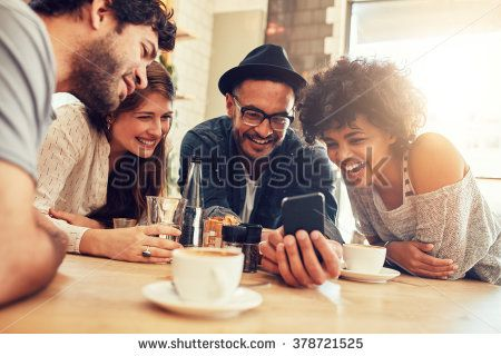 Portrait of cheerful young friends looking at smart phone while sitting in cafe. Mixed race people sitting at a table in restaurant using mobile phone. - stock photo