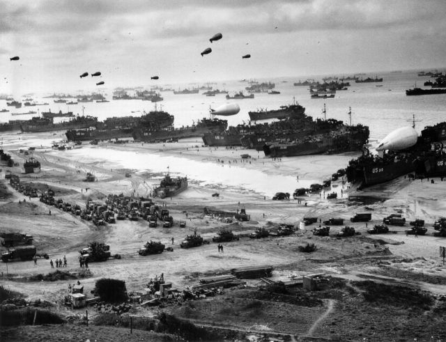 Operation Cobra, 1944: Breaking Out of Normandy. Landing ships putting cargo ashore on Omaha Beach, at low tide during the first days of the operation, mid-June, 1944.