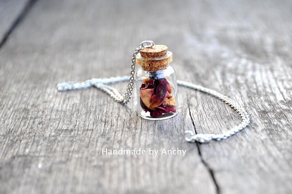 Small bottle with real dry red and yellow rose petals and