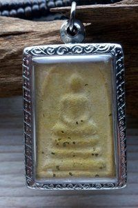 Buddha amulet uit Thailand / Amulet Boedha Aardewerk amulet met Boedha afbeelding in zilverkleurig `doosje`. Het doosjes is aan alle zijden bewerkt met mooie graveringen. Afmeting: 28 x30 x 17 mm....