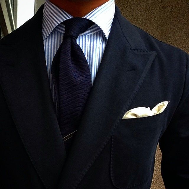 Navy jacket, white shirt with navy candy stripes, navy tie