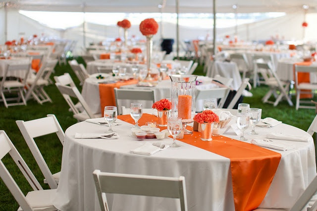 white table clothes, orange satin table runner, blue vases with white and orange flowers, blue votive candle holders