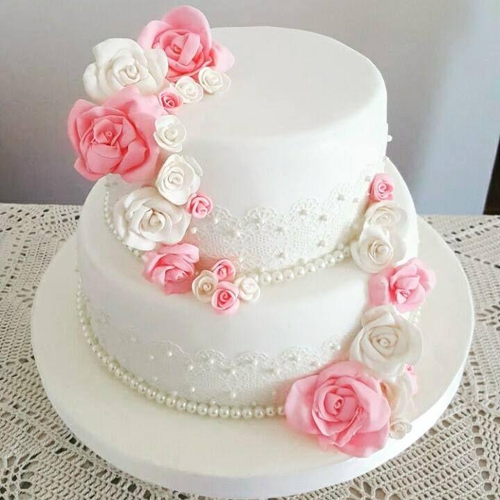 Torta de bodas de dos pisos con puntillas y flores comestibles.