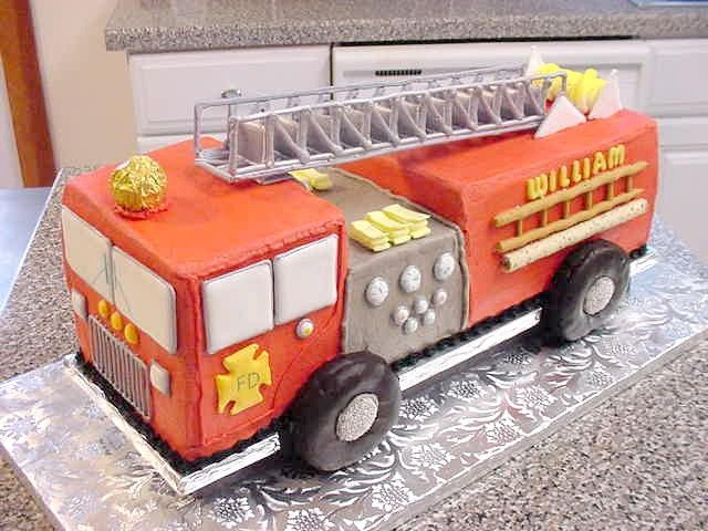 """3-D Fire Truck Cake - This is a 3-D Fire Truck iced in red and gray bc. Top extension ladder, side ladders, folded hoses, front grill and reeled hose are royal icing. Windows, FD crest, dials and knobs are color flow. The wheels are chocolate donuts with nonpariells for hub caps. The custom made cake base is raised 1"""" on a black pedastal to provide the illusion that the truck is riding on its donut wheels"""