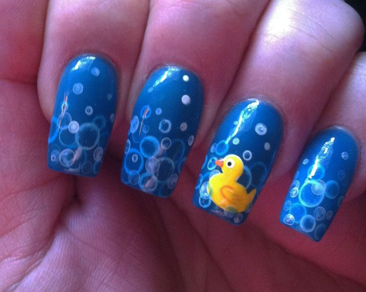Rubber duck nails. For the bubbles: mix water with white acrylic paint and blob a dot on the nail. Wipe brush dry. Wait about 30 seconds then touch the dry brush to the center which will suck the paint up and leave the ring.