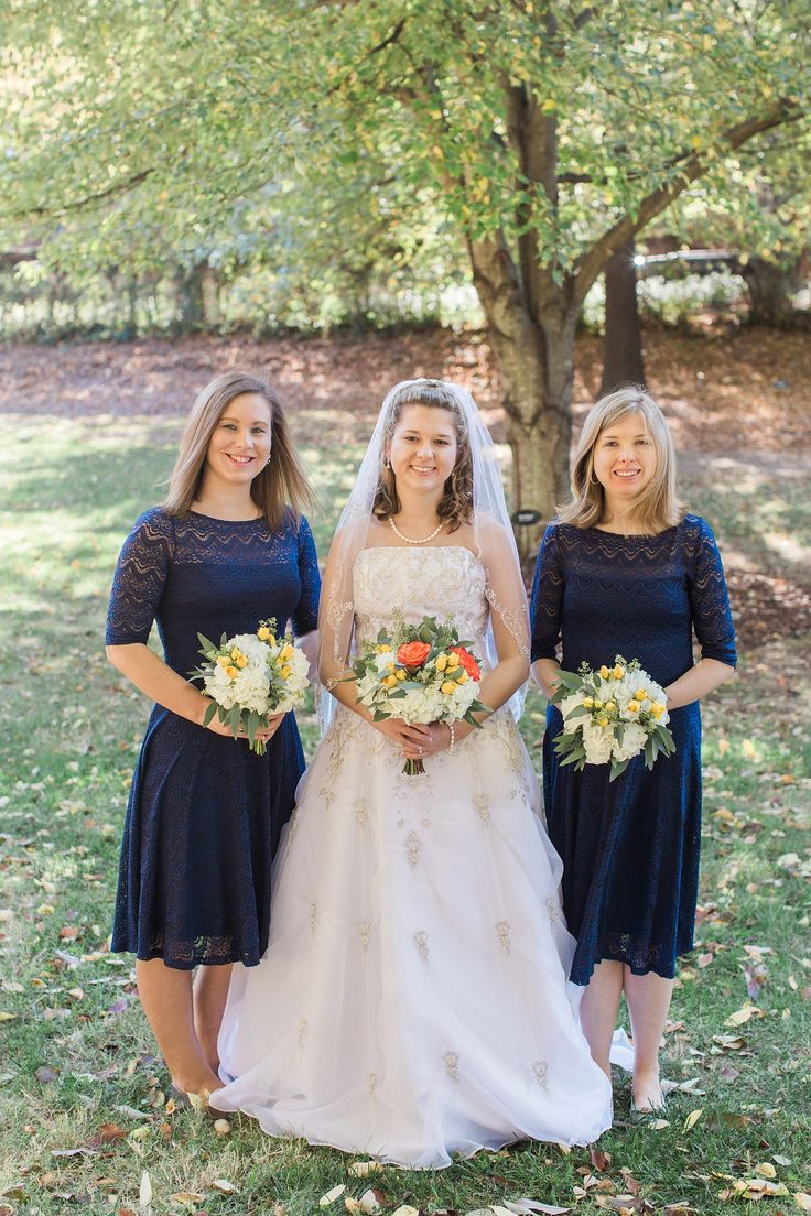 Navy blue crochet bridesmaid dresses with white, yellow, and orange flower bouquets.