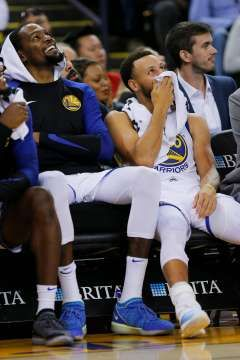 8ac47dc1ff34 Golden State Warriors forward Kevin Durant (35) and guard Stephen Curry (30)  share a laugh on the bench during the first half of an NBA preseason game  ...