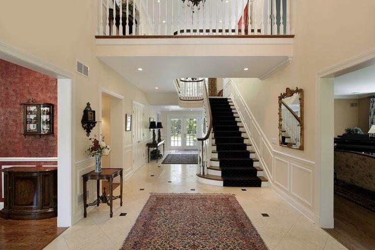 Hall de entrada com vista de desembarque superior que conduz à escadaria reta.  Salão foyer flui através de toda a casa para portas de vidro duplo que dão para a área da piscina no quintal.