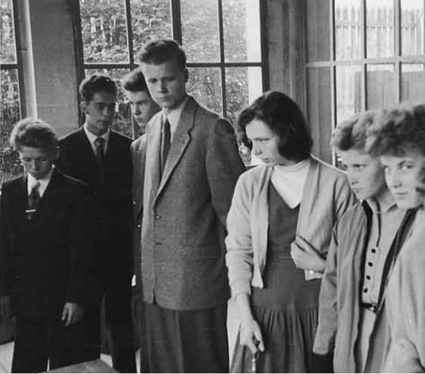 Die neuen kaufmännischen Lehrlinge lernen ihre Arbeitsumgebung kennen. Zukünftige kaufmännische Angestellte tragen Anzug und Schlips (50er Jahre).