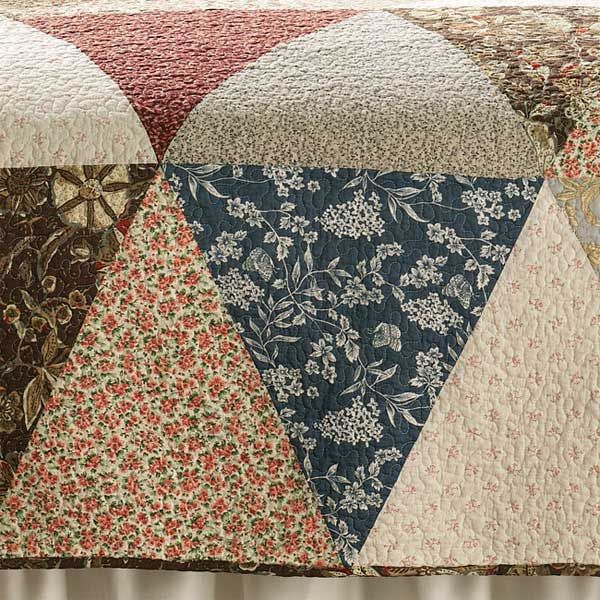 """A patchwork of florals and lighthearted prints are pieced together for this soft and lovely quilt. Quilted with vermicelli stitching, it has a pure cotton face, fluffy cotton fill, and ticking-stripe polyester-microfiber back. Sham 20"""" x 26"""". Patchwork quilt in multi. Washable. Imported."""