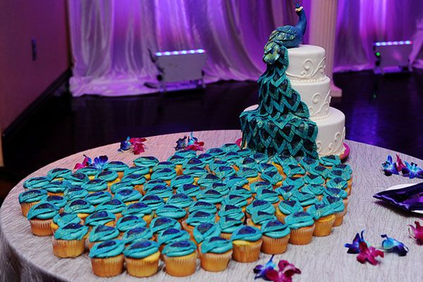 Love how the peacock feathers cascade into cupcakes!