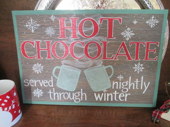 Gorgeous one-of-a-kind hand painted and hand lettered wooden sign.  Sign reads Hot Chocolate Served Nightly Through Winter lettered in red and white with a dark brown weathered background and green border, and beautiful mug and snowflake detailing.  Dimensions are 16 x 10 3/4 x 1/4  Easy to hang with wire backing already installed. This sign will look perfect at your holiday party or as part of your cozy home decor this winter!  Note: No stencils, computer generator or vinyl lettering is…