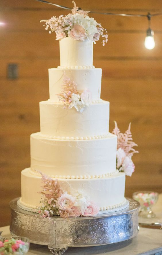 Glamorous five tier white wedding cake topped with blush flowers; Featured Photographer: Jennifer Yarbro Photography