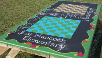 picnic tables with chess / checkers boards painted on top, and even some chalkboard paint areas-- multipurpose tables!