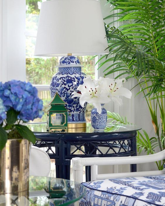 SWI Vintage A wonderful Chinoiserie vignette with bamboo furniture, a blue and white ginger jar lamp, a green pagoda candleholder, and blue and white Chinese fabric on the chair.