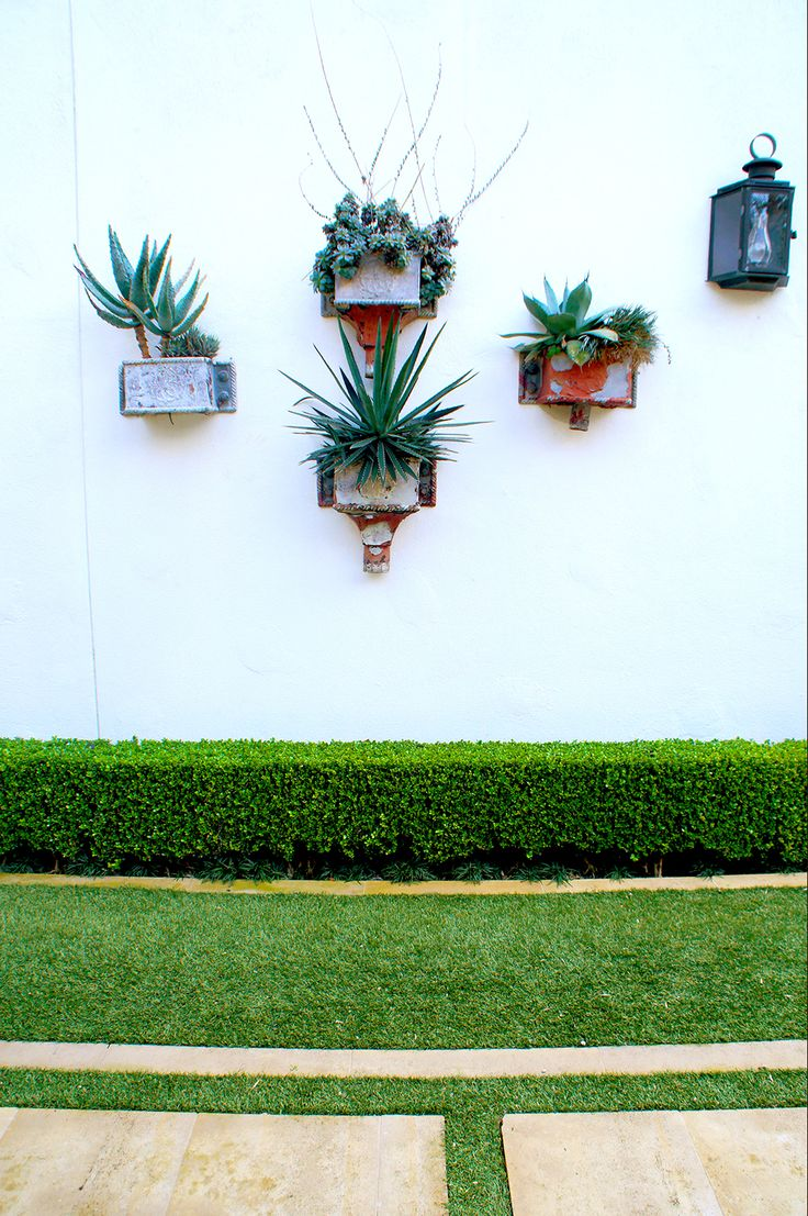 Succulent wall planters are displayed on the garage exterior.