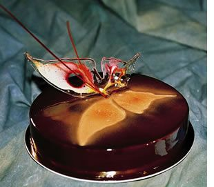 "Recipe for ""Papilio"". This entremet - which is made of a chocolate mousse, a chocolate cremeaux, an exotic caramel enclosed between two layers of chocolate biscuits and an almond croustillant - is one of the recipes by the French team, winner of the Coupe du Monde de la Patisserie – World Pastry Cup 2003."