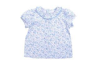 Blusa para bebe niña en tela estampada con florecitas azules. Cuello redondo con vuelo en el borde y mangas cortas. Se abotona en la espalda.