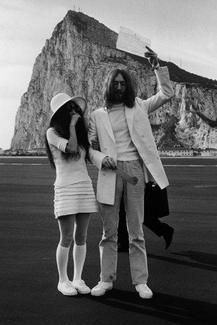 "John Lennon and Yoko Ono, 1969 John Lennon and Yoko Ono were married in Gibraltar and promptly took part in an anti-war ""bed-in"" following the ceremony. Zsa Zsa Gabor was not pleased with the couple's attire and said they looked like ""two people going to hold up a bank."""