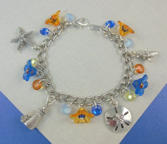 Edie ~ Beach Charm Bracelet for Girls in Cobalt and Tangerine  On the wrist at 6 1/4 inches, Lilly is a lovely charm bracelet for the little beach lover in your life. With lead free pewter charms of a starfish, lighthouse, sand dollar, and conch shell, this bracelet will surely bring back fond memories of a beach vacation or a memorable day at the beach. What a great gift to announce your vacation plans!  On a silver plated cable chain that closes securely with a lobster claw clasp, your...