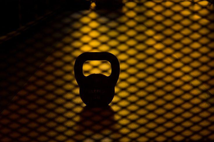 Το σκοτεινό περίγραμμα εξοπλισμού του γυμναστηρίου φωτογραφημένο μέσα από ένα σιδερένιο πλέγμα.