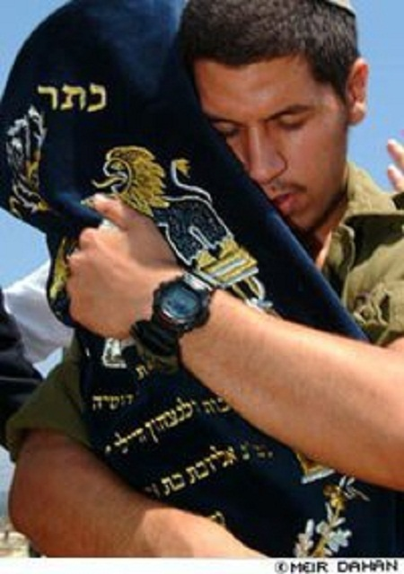 IDF Soldier embraces Torah - Loving the Word of God that tells how He gave the land of Israel to the Jewish nation, praying for its peace always.