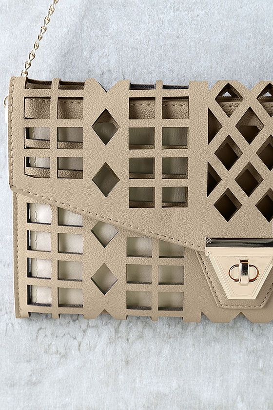 """Great things are taking shape, and the final product is the Geo du Jour Cutout Taupe Clutch! Taupe vegan leather is covered in geometric cutouts for a style that's totally chic and unique. Front flap boasts a shiny gold twist-lock closure that opens to reveal taupe lining in one main compartment, with a small zipper pocket at back. Carry as a clutch or clip on the 46"""" long gold chain strap."""