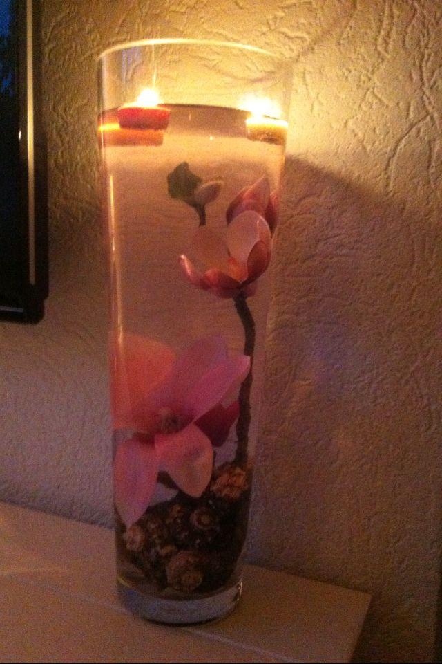 Twee kunstbloemen verzwaren zodat het onder water blijft in een grote vaas met water. Wat decoratie onderin. Bijv. stenen of schelpen. Dan een waxinelichtjes op laten drijven.