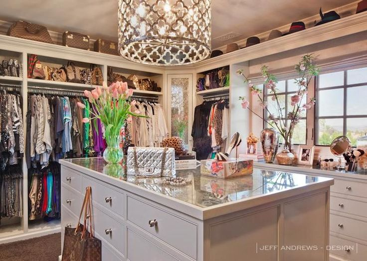 Khloe Kardashian - Luxurious walk-in closet with double hung clothes rails alongside built-in dresser below windows as well as ceilings with upper shelf adorned with Louis Vuitton luggage and an assortment of hats. The custom closet features a antiqued mirrored top closet island accented with nickel hardware below a gold quatrefoil pendant, Ironies Asilah Chandelier.