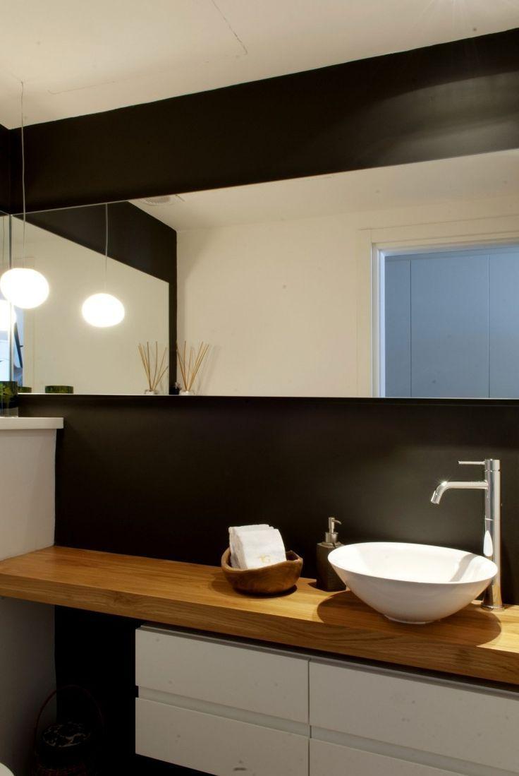schönes Bad mit Waschtisch aus Holz und schwarzer…