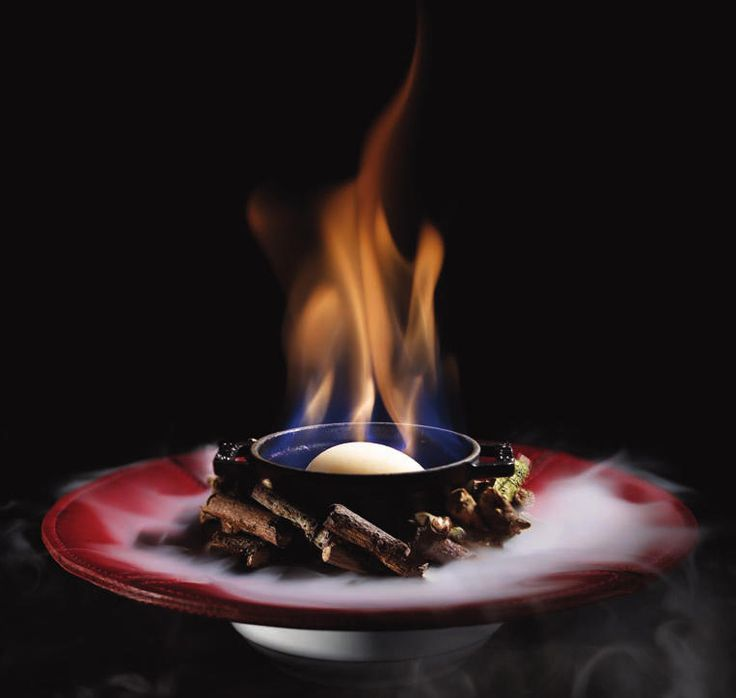 """""""Flaming Sorbet"""" is a dish designed to mimic a campfire, made of sorbet made with gellan, special gelatin that can withstand high heat. Whiskey is poured on top and ignited, as the sorbet magically remains frozen. The bowl sits on a bed of twigs with dry ice hidden beneath it. A perfumed mixture of leather, wood, tobacco, and whiskey is poured over the twigs, creating a cascade of vapor around the dish, releasing nostalgic aromas of a campfire. By molecular gastronomy chef Heston Blumenthal."""