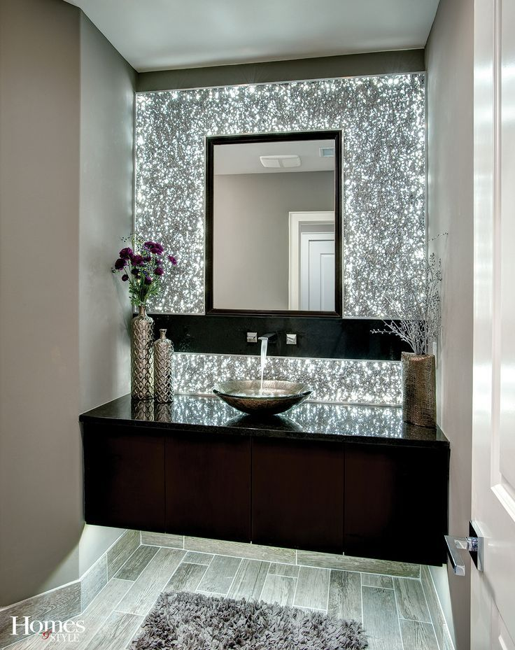 The centerpiece of this spectacular powder bath is the L.E.D. backlit extruded aluminum wall panels which give this room an ambiance that is unparalleled. The floating vanity with accent lighting, an amazing art glass vessel sink, beautiful solid surface top, and designer faucets flowing from the wall complete this one-of-a-kind room.: – Hannah Levi Flores