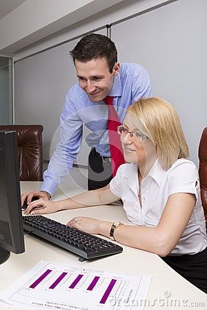 Happy business women and men working on computer in their office.