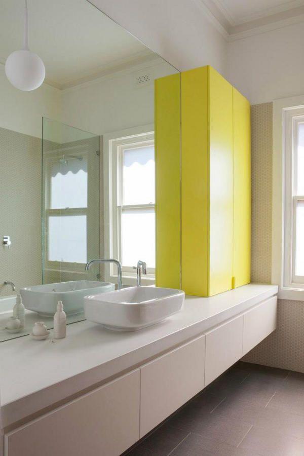 baño, lavabo sobre encimera y cajones, bañera con mampara para ducha, blanco con armario amarillo como contraste