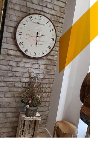 Un reloj antiguo, unas flores secas y una pared con paneles de ladrillo macizo de MSD
