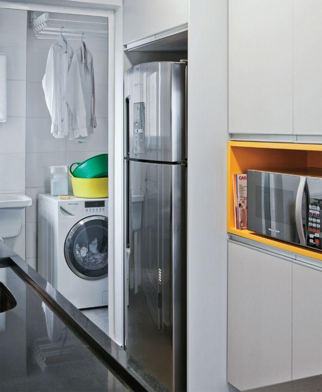 """Os móveis planejados da cozinha são revestidos de laminado cinza-claro, repetindo o tom do rebaixo de gesso e das paredes. """"Escolhemos um módulo amarelo, do micro-ondas, para trazer um pouco do visual da sala para a marcenaria e, assim, integrar ainda mais os ambientes"""", explica Cristiane. Uma porta de vidro e alumínio separa a área de serviço. Marcenaria, Bufê (no jantar), armários de cozinha, nicho sob a bancada, rack e painel de MDF no estar (JS Marcenaria, R$ 11100)."""