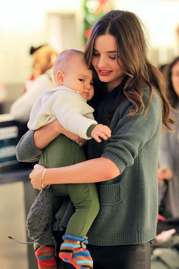 Miranda Kerr and Flynn. OMG BABY BOOTIES IN A FOREST GREEN ONESIE. kinda dying over here.